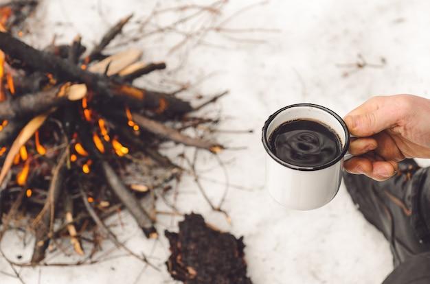 Male hands hold a mug of coffee near a burning campfire.