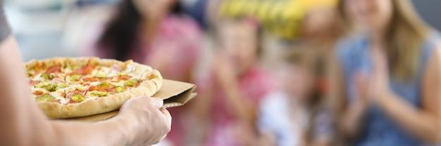 남성의 손에 사람들의 배경에 피자를 개최.