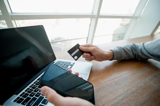 男性の手は、バックグラウンドでラップトップとスマートフォンとクレジットカードを保持します。疑わしいサイトにクレジットカードの詳細を入力しないでください。カードを使用してオンラインで購入する男性。金融リテラシーの概念。