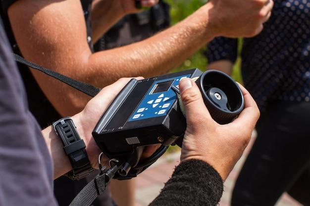 Мужские руки держат беспроводную систему следования за фокусом во время съемки.