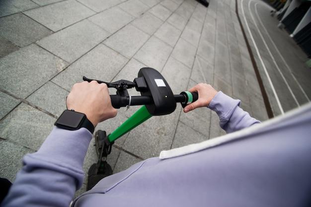 男性の手はe-スクーターのハンドルを握っています。上面図。簡単運転コンセプト。一人称ビュー。街中を電気で運転している男。環境にやさしい輸送コンセプト。
