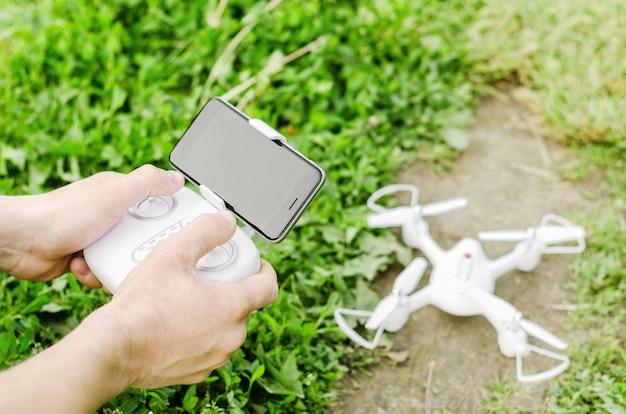 草とドローンの背景にquadrocopterからスマートフォンを使ってリモコンを持っている男性の手。現代の技術、飛行の概念。