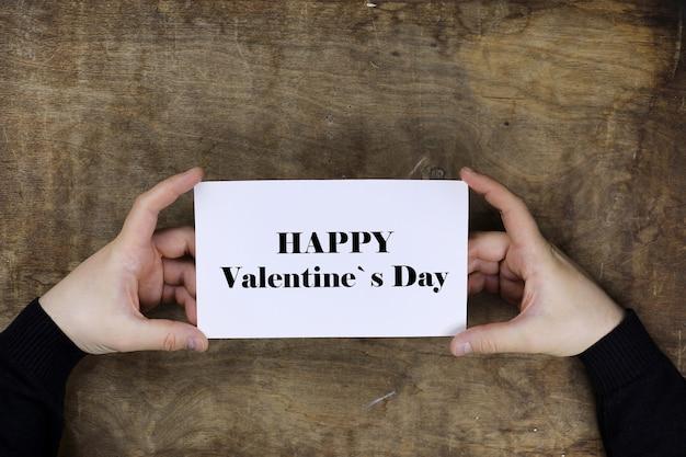나무 질감 테이블의 배경에 흰색 빈 종이 해피 발렌타인 데이를 들고 남성 손