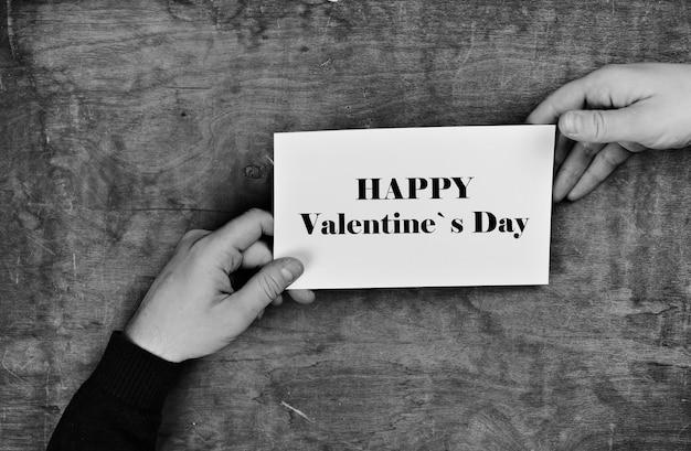 나무 질감 테이블 해피 발렌타인 데이의 배경에 흰색 빈 종이를 들고 남성 손
