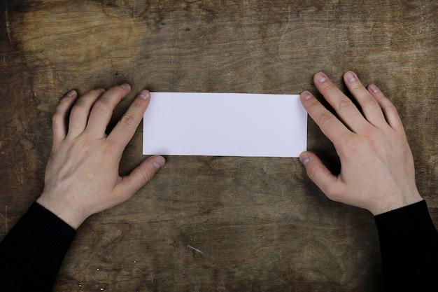 木製のテクスチャテーブルの背景に白い空白の紙を保持している男性の手