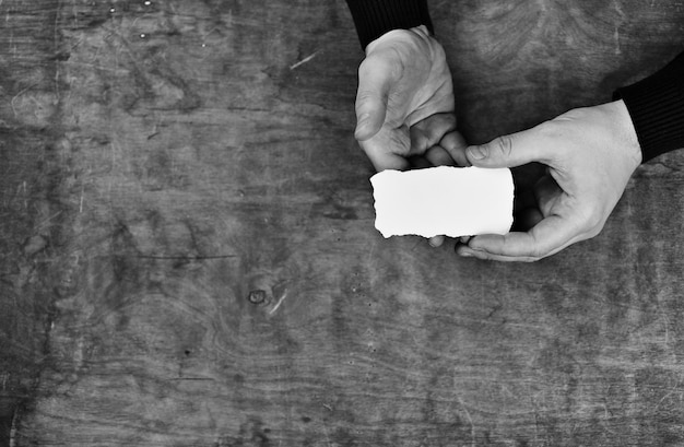 나무 질감 테이블의 배경에 흰색 빈 종이를 들고 있는 남성 손