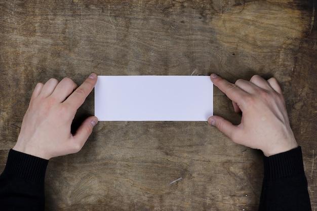 木製のテクスチャテーブルの背景に白い白紙の紙を保持している男性の手