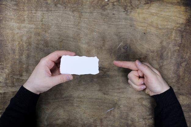 Мужские руки держат белый чистый лист бумаги на фоне деревянного стола текстуры
