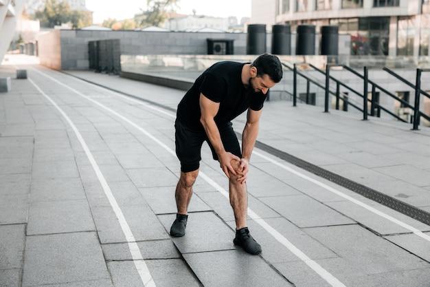 痛む膝を保持している男性の手。屋外でジョギング中に足に痛みを感じる強い男。閉じる。黒のスニーカーを履いた男性ランナーが立っていて、左足にけいれんを感じています。ビューをカットします。