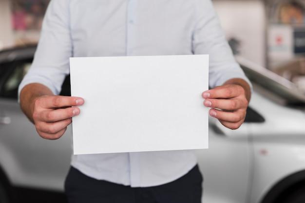 Mani maschii che tengono una carta in bianco