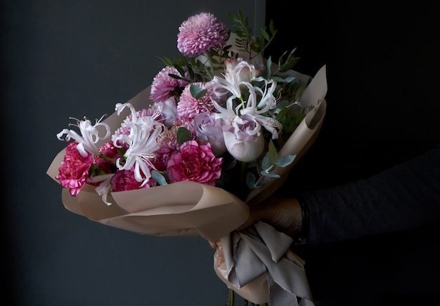 Male hands holding a bouquet decorated in vintage style on a dark background