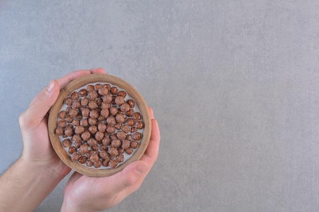 Mani maschili che tengono una ciotola di palline di cereali su sfondo di pietra.