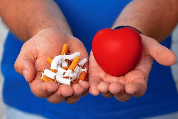 Мужские руки держат сломанные сигареты крупным планом, бросая привычку