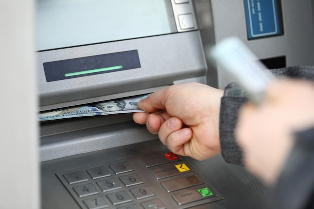 Male hands holding bunch of hundred dollars banknotes at atm machine