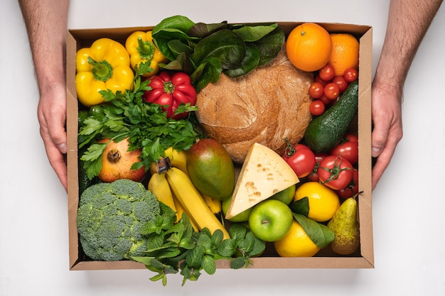 新鮮な食料品でいっぱいの段ボール箱を持つ男性の手
