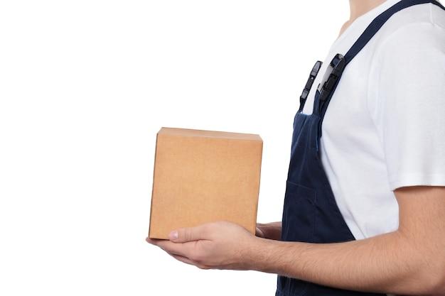 白い背景で隔離の段ボール箱を保持している男性の手。紺色のオーバーオールと白いtシャツを着た小包を持つ男の側面図。配信のコンセプト。