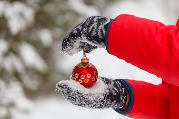 Male hands holding a christmas red ball. frosty winter day in snowy forest. merry christmas and happy new year theme