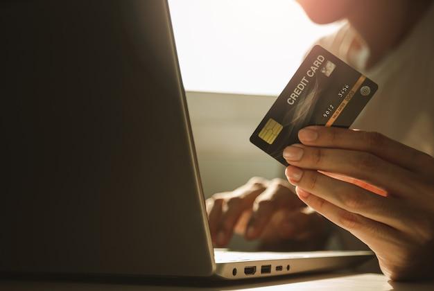 男性の手がクレジットカードを保持し、自宅の仕事、電子商取引、インターネットバンキングからの休憩中にオンラインショッピングのための作業机でラップトップコンピューターを使用