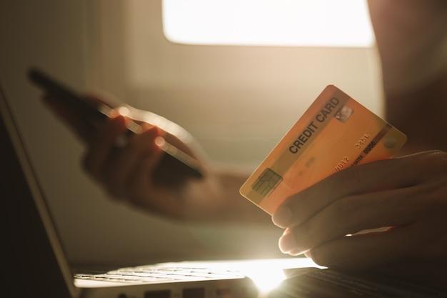 男性の手がクレジットカードを保持し、自宅の仕事、電子商取引、インターネットバンキングを休んでいる間、オンラインショッピングの作業デスクでスマートフォンを使用
