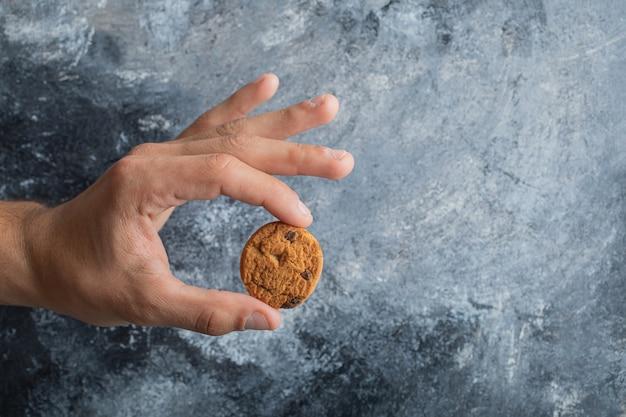 Mani maschili che tengono deliziosi biscotti con scaglie di cioccolato su fondo di marmo