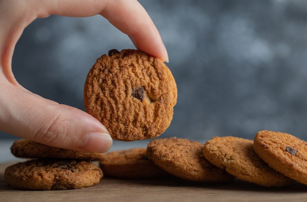 Male hands holding delicious chocolate chip cookies on marble background