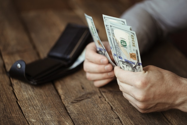 Male hands holding dollar banknote on old wooden table