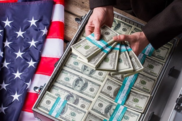 Male hands holding dollar bundles. hands, money and american flag. wealth and power. income of successful politician.