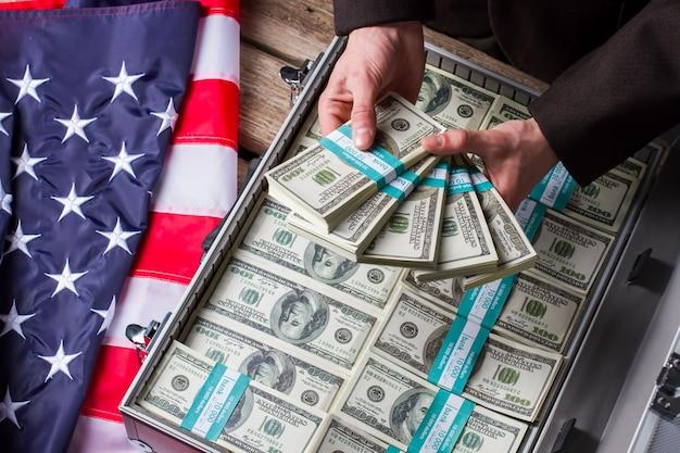 Мужские руки, держа пачки долларов. руки, деньги и американский флаг. богатство и власть. доход успешного политика.