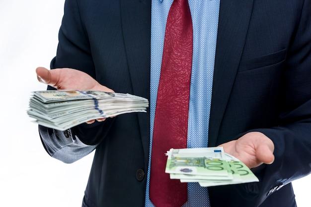 ユーロ紙幣とドル紙幣を持っている男性の手が閉じる