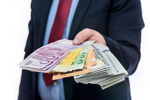 유로 달러 지폐를 들고 남자 손을 닫습니다.