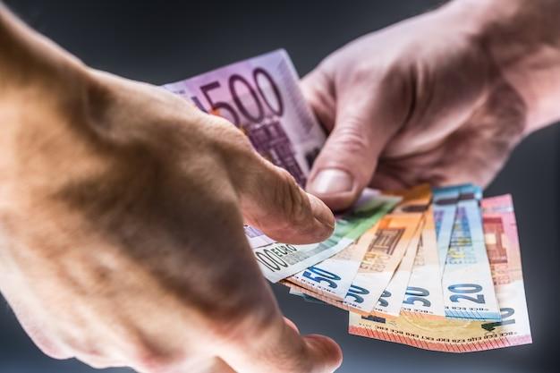 남자 손은 유로 지폐를 들고 다른 손은 뇌물을 받습니다.