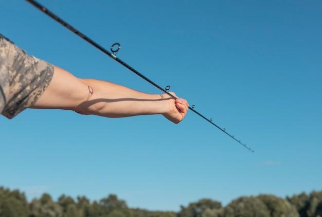 Мужские руки держат удочку и собирают ее над голубым ясным небом в летнее время