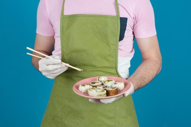 Mani maschili che tengono i rotoli di torta fresca fatta in casa su un blu.