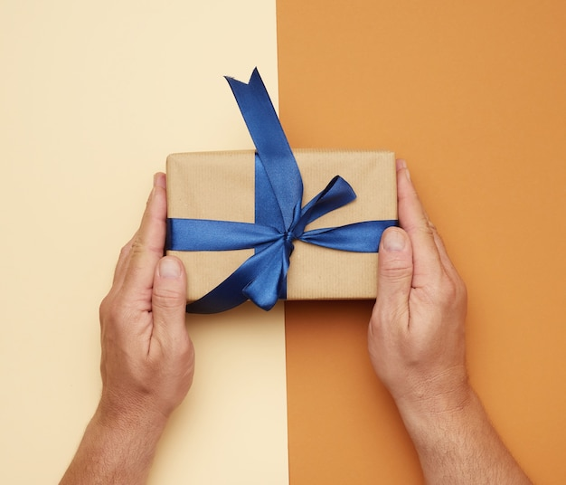 Male hands holding gift box with a bow
