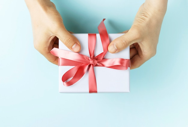 Male hands holding gift box with ribbon on blue background