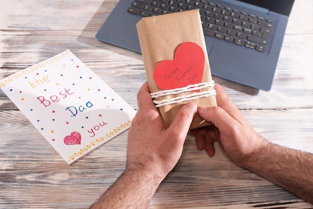Мужские руки держат подарок, завернутый в крафт-бумагу