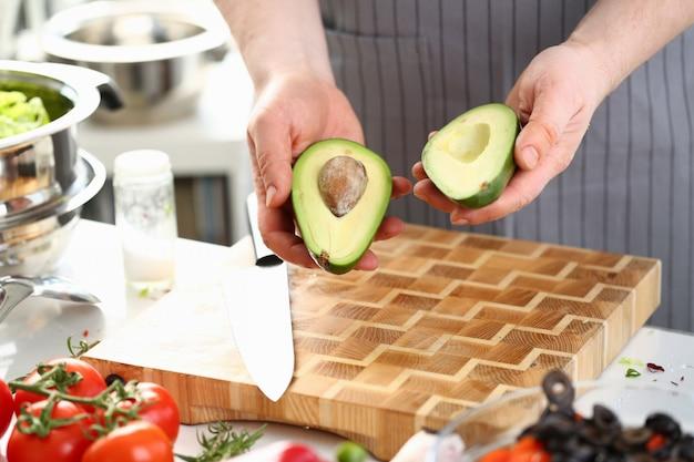 Male hands holding green avocado fruit halves