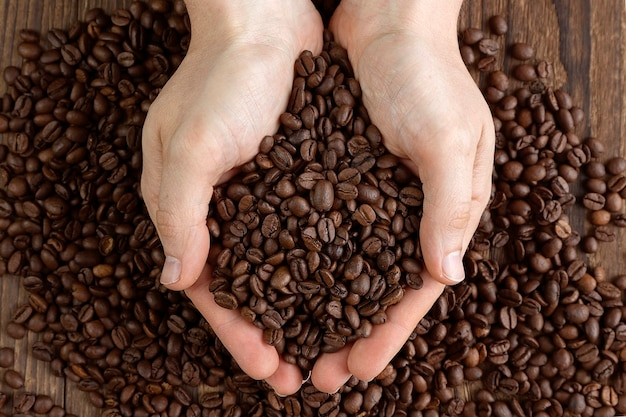 Male hands holding a handful of coffee beans on wooden table