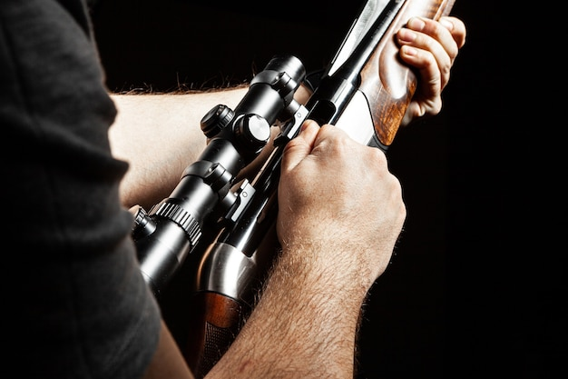 Male hands holding hunting rifle on black background close up