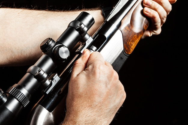 Male hands holding hunting rifle on black background