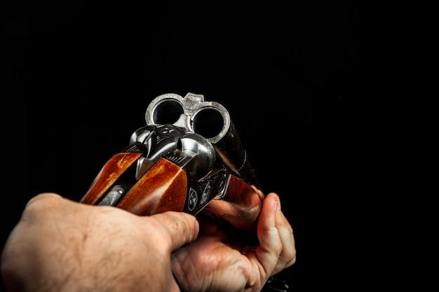 Мужские руки, держа охотничье ружье на черном фоне