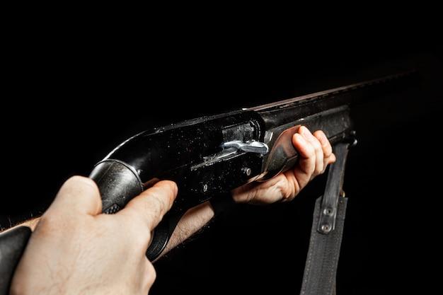 Мужские руки держат охотничье ружье на черном фоне