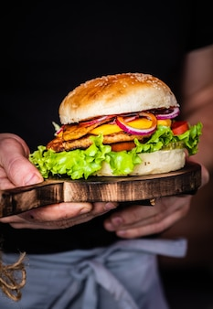 Male hands holding a juicy tasty cheeseburger with beef, lettuce, pickles, tomato and onion rings on a wooden table. classic street food - grilled burger