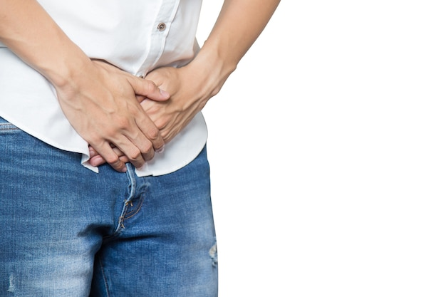 Male hands holding on middle crotch of trousers with prostate inflammation