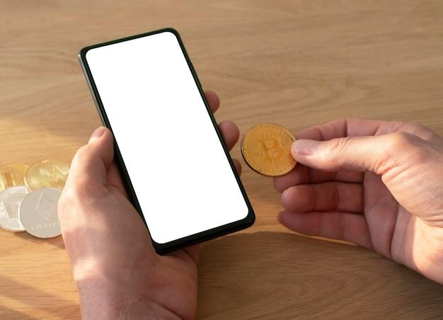 モックアップとビットコインコインの画面と木製のテーブルの上に手で携帯電話を保持している男性の手。
