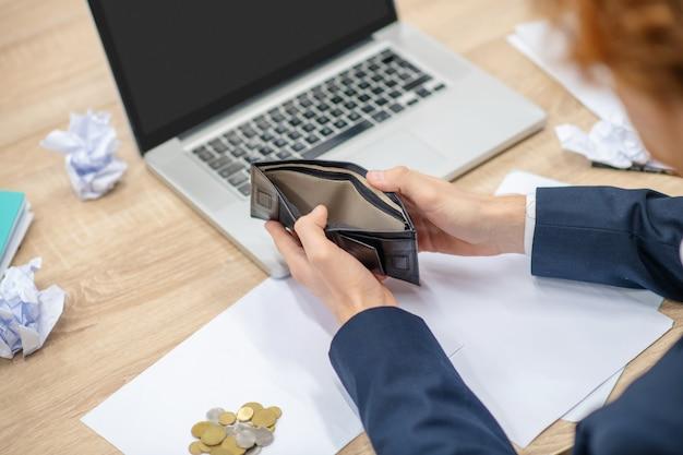 開いた空の財布をオフィスの作業台の上に保持している男性の手、顔が見えない