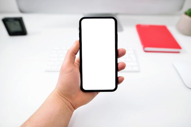 男性の手は、オフィスのテーブルの上に隔離された画面で電話を保持しています。