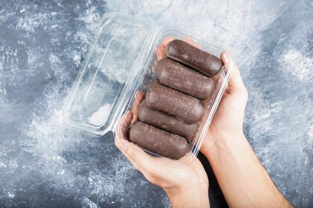 Мужские руки держат пластиковую коробку шоколадных палочек на каменной поверхности