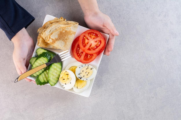 石のテーブルで朝の朝食とプレートを保持している男性の手。