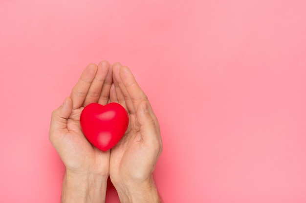 Male hands holding red heart in hands on pink background happy valentine's day